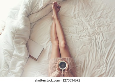 Close up legs women on white bed. Women reading book and drinking coffee in morning relax mood in winter season. Lifestyle Concept