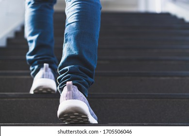 close up legs of young businessman while walking up the stairs in the modern city with the sunspot background. Go up, success, grow up concept.