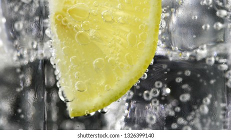 Close up lemon, lime slice in soda water bubbles.