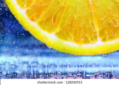close up of lemon slice under water with bubbles on blue background