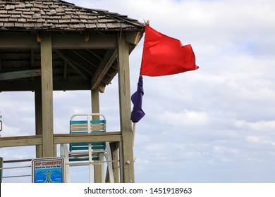 close up lifeguard tower with red waving flag over windy seascape view