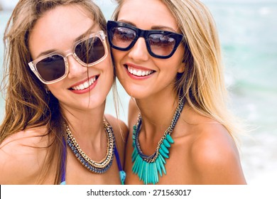 Close up lifestyle fashion portrait of two pretty fresh young brunette and blonde best friends girls, having vacation on the tropical island beach, wearing bikini sunglasses and bright jewelry .