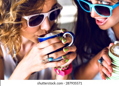 Close up lifestyle image of two young women drinking morning coffee speaking and gossip, bright stylish clothes sunglasses and accessorizes. two girls drinking cappuccino in cafe.