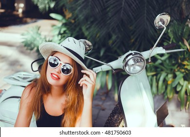 Close up lifestyle image of young fashionable woman in casual outfit sitting on scooter on the street. Wearing blue shirt, white pants, trendy sunglasses. Tourist woman enjoying holidays