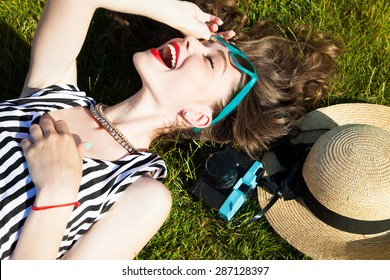 Close up lifestyle portrait of cheerful brunette hipster girl going crazy making funny face and showing her tongue.Laying on the ground and laughing.Bright colors,urban street background.accessories