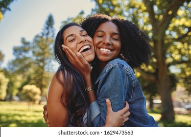 Close up lifestyle portrait of diverse multiracial happy best friends hugging each other and laughing in the park