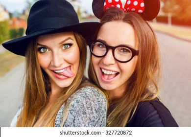 Close up lifestyle  portrait  of  girls best friends makes funny  grimaces on camera , show tongue  and laughing together.Two women posing outdoor, warm sunny evening colors.