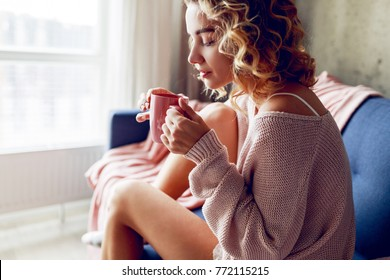 Close up lifestyle portrait of   pensive woman drinking   coffee in early morning, sitting on coach in pink cozy sweater.