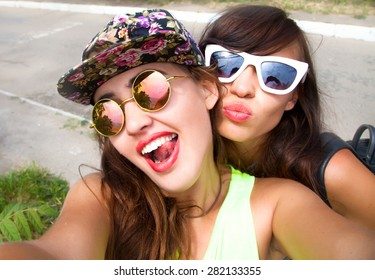 Close up lifestyle portrait of two pretty fresh hipster young brunette and blonde best friends girls,make selfie and having fun.Wear summer sunglasses and make photos,of their weekends.Selfie portrait