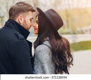 Close up lifestyle  portrait of young stylish glamour girl and guy in love . Couple walking down the street in sunny fall . Warm  colors. Wearing black trendy outfit . Romantic mood.