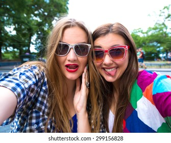 Close up lifestyle selfie portrait of pretty fresh young brunette and blonde best friends girls sisters making selfie,having fun, wearing sunglasses. Fresh make-up,teenage outfit,summer vacation.