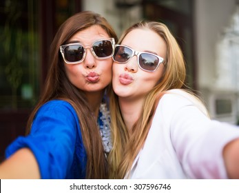 Close up lifestyle selfie portrait of two young positive woman having fun and making selfie, teenage hipster trendy clothes and sunglasses, long hairs,fresh make up. happy together. sisters, friends