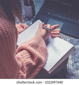 Close up lifestyle soft image of pretty young woman sitting on her cozy bed and making notes to her diary. Fall season mood. Bright colors.