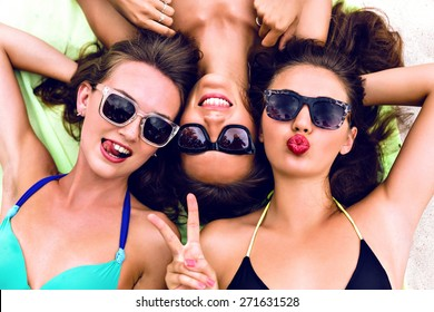Close up lifestyle summer portrait of thee girls friends relaxed and getting sunbathe, laying on the beach, wearing bright bikinis and stylish vintage sunglasses. Swing tongue, sending kiss.