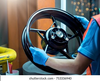 Close up light alloy car wheel in process QC worker checking dish rim.