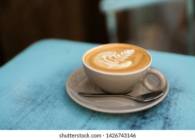 Close up of a light brown fresh mocha with beautiful latte art outdoors on a light blue table a cafe in Paris.