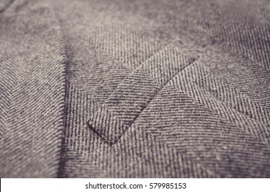 Close up of light grey tweed woolen coat or jacket with a pocket fragment.