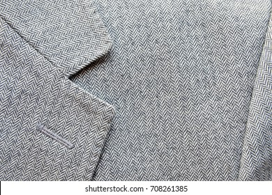 Close up of light grey tweed or woolen jacket with a collar fragment.