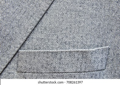 Close up of light grey tweed or woolen jacket with a pocket fragment.