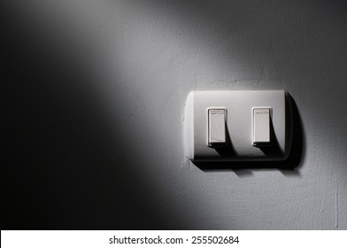 Close up of light switch with sunlight and shadow on white background, turn on and turn off, copy space, In the dark