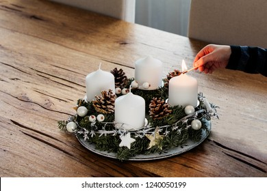 Close up of lighting the first candle on Advent Wreath on the first Sunday in December. Celebrating Christmas holidays, swiss tradition. Crop hand holding the safety matches to light the candle.