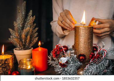 Close up of lighting first candle on Advent Wreath Celebrating Christmas or new year holidays. warm lights, xmas tree winter home interior decorations. hand holding match to fire candle. Wallpaper