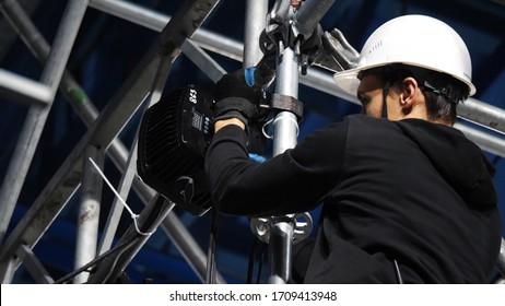 Gros plan sur un technicien d'éclairage installant un équipement d'éclairage professionnel pour la scène de concert. Vidéos de stock. Installation de lampes et de projecteurs pour l'événement.