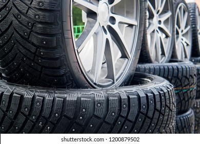 A close up of a lined winter studded wheels set outdoors. Close up of the studs and protectors on tires installed on the street. Winter tires positioned outdoors. Rows of exposed snow tires.