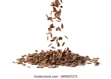 Close up of linseeds or flax seeds falling down in a pile and isolated on white background
