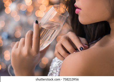 Close up lips of attractive young Asian girl with glass of champagne. Sexy dressed girl in sparkle dress drink alcohol while standing in front of Christmas Tree. Happy New Year and 2018 Christmas.