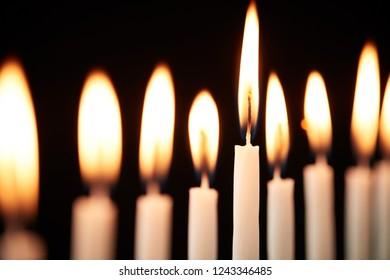 Close Up Of Lit Candles On Metal Hanukkah Menorah Against Black Studio Background