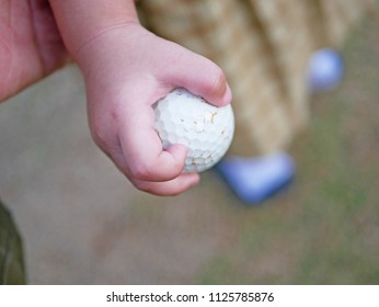 Close up of little Asian baby girl hand grasping a golf ball firmly by herself - encouraging development of baby's eye and hand coordination by letting them use their hands and fingers more often