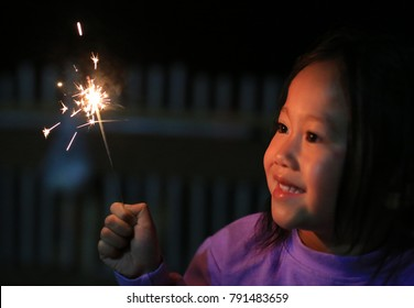 Close up little Asian girl holding fire sparklers.