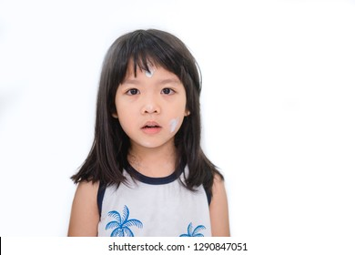 Close up of little asian girl putting sun screen cream on her face isolated on white background.summer vacation and protection face skin from sun.