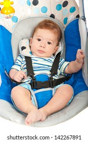 Close up of little baby boy in blue electric swing
