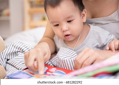 Close up of little baby while the baby learning to reading from mother or looking at the book on the mother's hands (education baby or baby growing up concept) (soft focus)