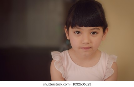 close up of little ballerina girl's smiling face with blurred background, filtered tones