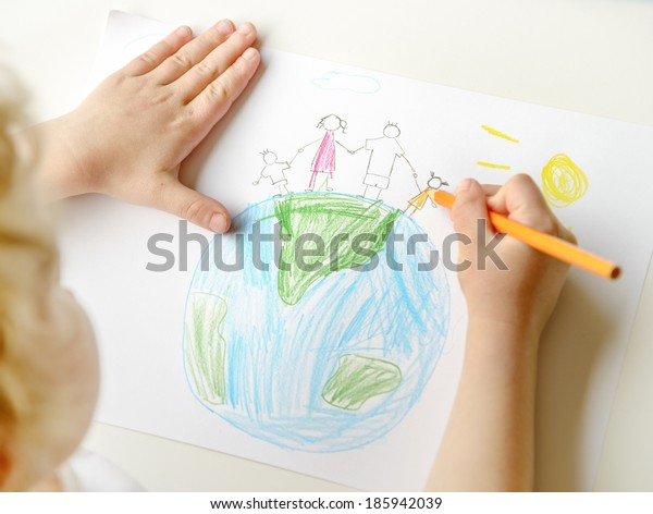 Close up of little blond child drawing a happy family standing on globe