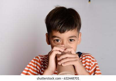 Close up of little boy drinking chocolate milk