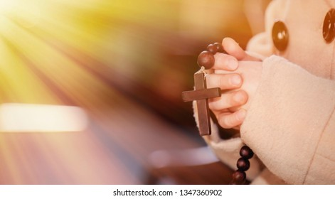 Close up little child girl with rosary beads praying in the church. Faith, religion concept.