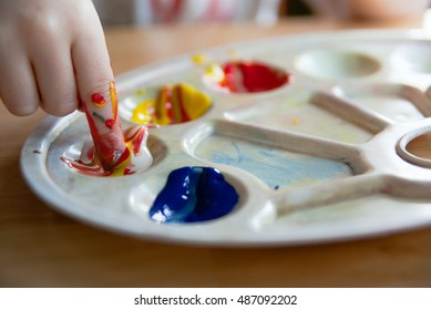 Close up of little child playing with fingerpaint colors.