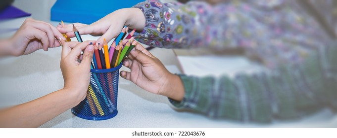 Close up little children hands pick up color pencils, home school and back to school education background and banner concept