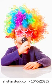 Close up little cute child girl wearing sunglasses with colorful wig singing in microphone. Singer talent and vocal training concept.