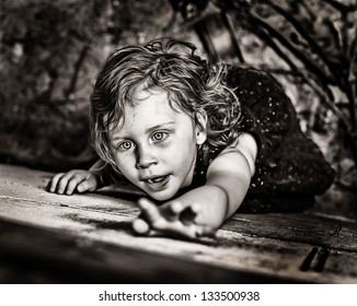 Close up of little girl dramatically reaching up on grubby wall