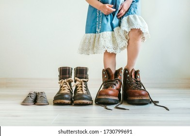 Close up of little girl in  dress putting on father's hiking shoes. Father's, mother's and kids boots standing in a row indoor. Family concept. Selective focus on the boots.