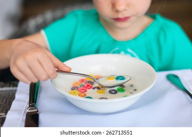Close up of a little girl eating cereal with milk for breakfast in restaurant