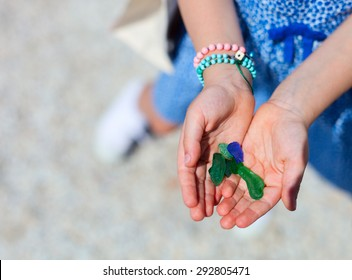 Close up of little girl hand holding variety of colorful sea glass