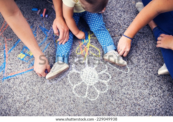 Close up of little girl and her parents drawing with chalks on the sidewalk