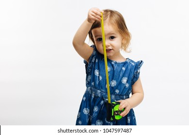 close up of a little girl holding measuring tape
