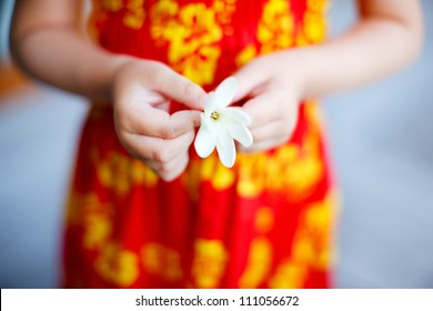 Close up of little girl holding tahitian tiare flower